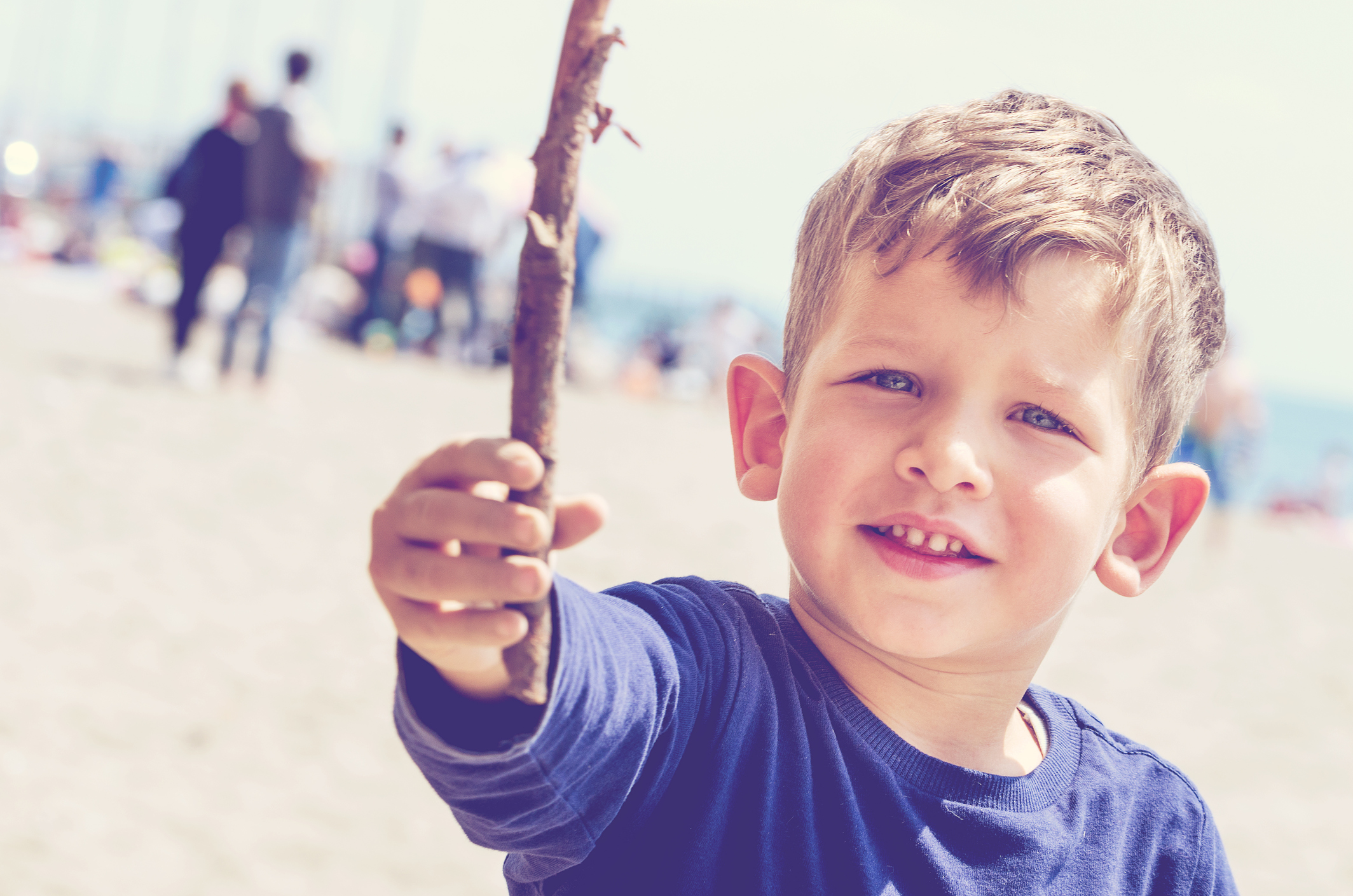 child gives you a stick while playing on the beach on a beautiful sunny spring day